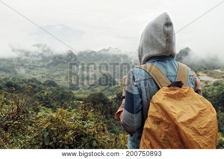 Hiker with a backpack look at the mountains in the rain. Adventure and traveling along mountains in cold weather freedom and active lifestyle concept