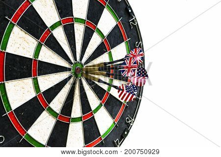 Metal darts have hit the red bullseye on a dart board. Darts Game. Darts arrow in the target center darts in bull's eye close up isolatedon white background.
