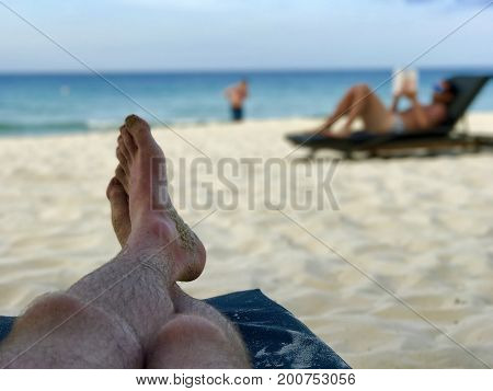 Legs on a beachchair and blurry man reading a book on white sand beach and sea view