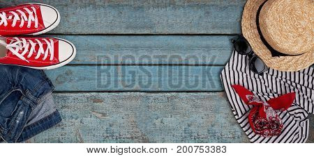 Still life of various items for recreation clothing hat sneakers camera passport telephone sunglasses tickets headset on a wooden blue background. Concept of youth travel light economy.