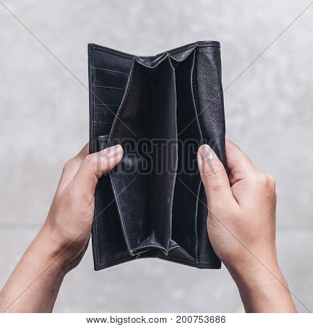 Top view image of woman's hands open an empty black leather wallet with floor background