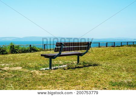 Empty Bench On A Hill On The Ocean Shore, Green Lush Vegetation, A Wooden Bench