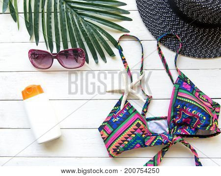 Summer Fashion woman bikini big hat and accessories and sunglasses go to travel in the beach. Tropical sea.Unusual top view background. Summer Concept.