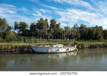 Old White Boat Moored To Shore