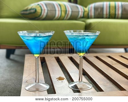 Blue a nd yellow cocktails in martini glasses on coffee table and green sofa with strippes cushion