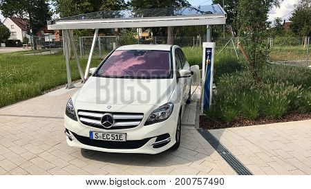 Stuttgart - August 20, 2017: A Merceds B-CLass electric car is being charged in front of a carport covered with solar panels - concept for future sustainable and self-contained mobility