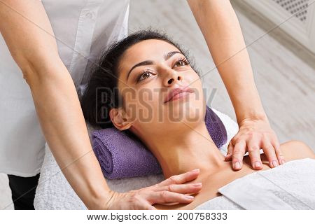 Neck massage in spa. Female beautician work in wellness center. Professional massagist make relax healthy procedure to beautiful indian girl in cosmetology cabinet or beauty parlor. poster