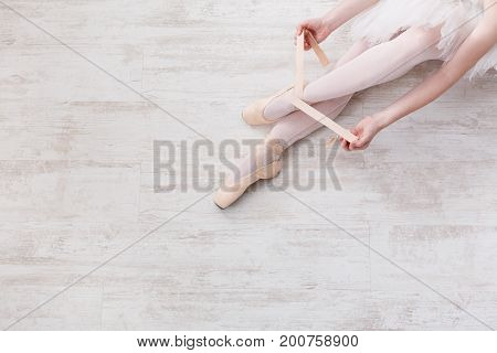 Ballet backgroung with copy space top view. Choreography and dancing classes concept. Beautiful legs of young ballerina putting on pointe shoes at white wooden floor background