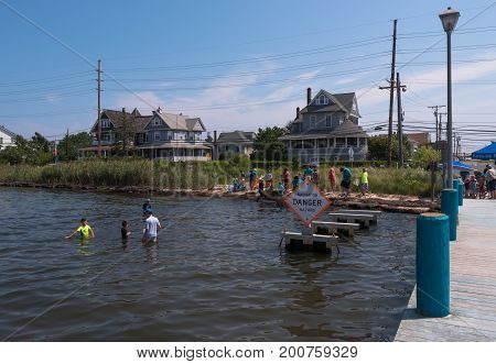 Seaside Heights NJ USA -- August 21, 2017   Young people are crabbing in shallow waters by a danger sign in Seaside Heights at the Jersey Shore. Editorial Use Only.