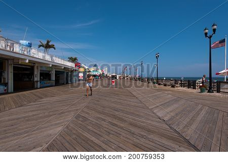 Seaside Heights NJ USA -- August 21 2017 -- A shirtless man wearing a hat is walking along the Seaside Heights boardwalk on a hot summer day at the Jersey Shore. Editorial Use Only.