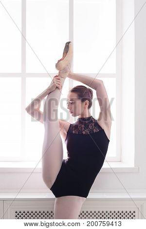 Beautiful ballerina in standing split. Classical ballet dancer portrait. Beautiful graceful ballerina in black at dancing class, copy space
