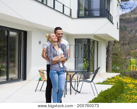 Portrait of a happy young couple hugging in front of their new luxury home villa