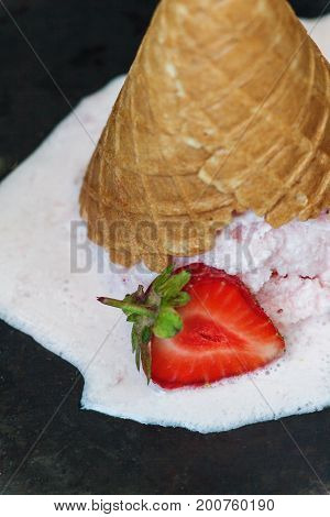 Strawberry ice cream in a waffle cone inverted and melted against a dark background, close-up.