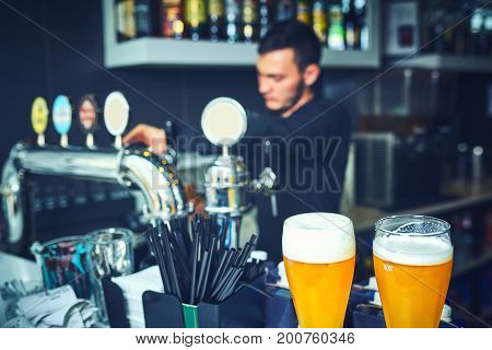 Close-up of young bartender pouring beer while standing at the bar counter.