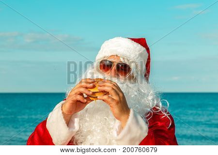 Santa Claus On The Beach Eating A Hamburger.