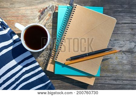 a girl with a cup of coffee and sits on a park bench. Notebooks for writing and books. Studies, work and business concept.