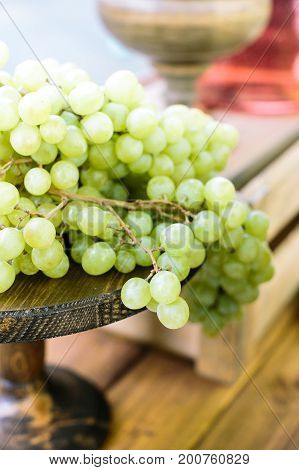 food, dining culture, freshment concept. in the wooden vase of rich dark color there are green juicy bunches of grape place on the dining table like decoration and refreshments