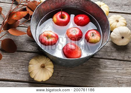 Autumn harvest background. Red ripe apples floating in clean water in metal basin, small pumpkins and dry leaves fall still life. Composition of fruits and vegetables on rustic wood with copy space