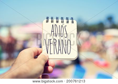 closeup of a young man in the seashore of a beach showing a spiral notepad with the text adios verano, good bye summer in spanish, handwritten in it