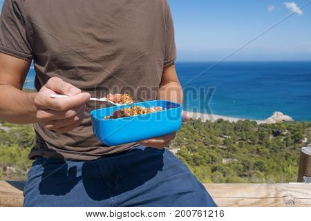 closeup of a young caucasian man eating a lentil salad from a blue plastic container outdoors, with the sea in the background