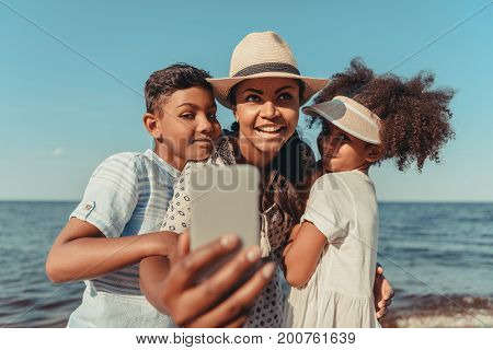 Mother With Kids Taking Selfie On Beach