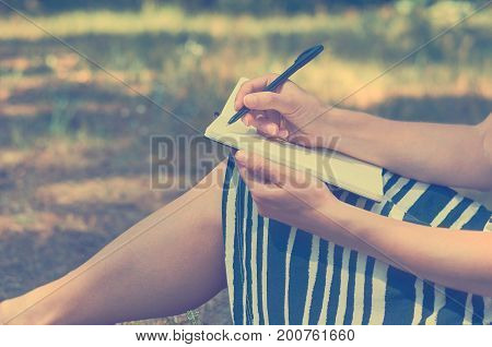 The girl writes in a notebook and studying in nature. The concept of freedom and unity,