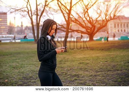 A beautiful young woman walking in a park in the sunset while using her phone