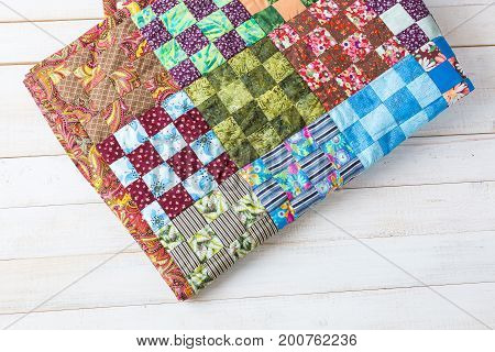 comfort, accessories, art, creation, style concept - original handiwork in asian traditions made of little textile squares in red, green and blue shades with such prints as flowers, leaves and strips