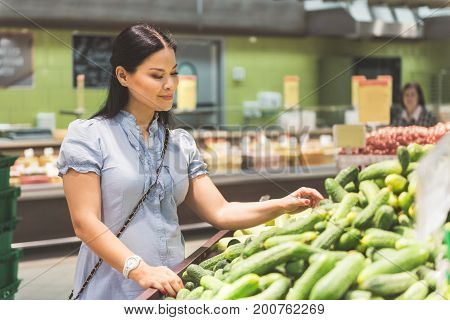 Female visitor expressing cheerfulness while buying cucumber in grocery department