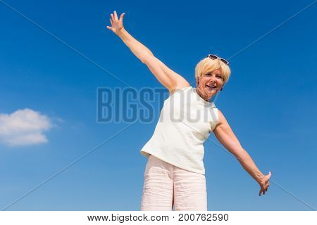Low-angle view of a fit senior woman looking up to the sky with outstreched arms while enjoying retirement in a sunny day of summer