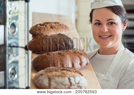 Baker woman presenting bread on board in bakery looking proudly into the camera