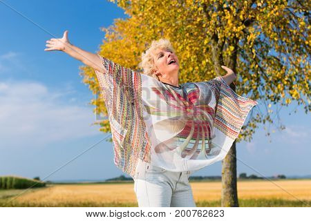 Active senior woman feeling free and happy while standing with outstretched arms outdoors on a field in a sunny day
