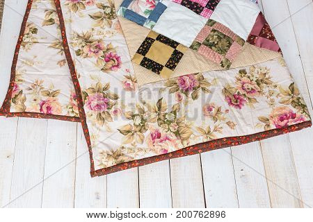 linens, warm, rest concept. pair of little hand maded blankets with flowery print decorated by ornament framed with geometric figures lying on the wooden floor in pile