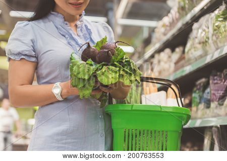 Focus on close up buyer arms keeping fresh bunch of vegetables and basket with products