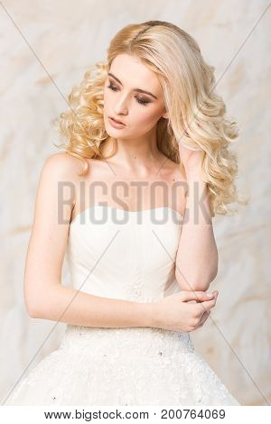 fashionable gown, beautiful blonde model, bride hairstyle and makeup concept - young romantic sensual lady in white wedding festive dress, standing indoors on light background, slender woman posing