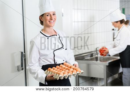 Chef in commercial kitchen taking eggs out of cold storage