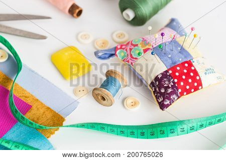 closeup sewing tools , patchwork, tailoring and fashion concept - working environment on a white table, thread spools, buttons, meter, pincushion, scissors, pieces of colored patchwork fabric, soap