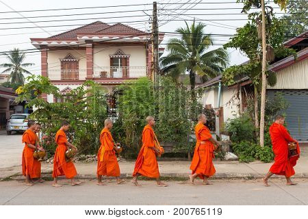 Vang Vieng, Laos - January 21, 2017: Buddhist alms giving ceremony in the morning in Laos