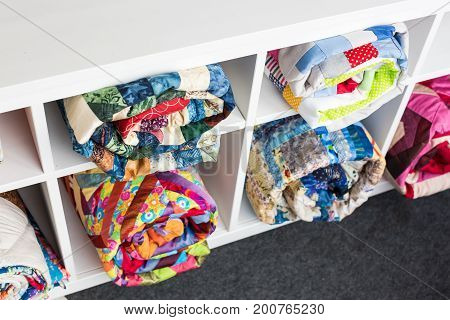 patchwork, sewing and fashion concept - colorful finished quilts in the studio at white shelves with few storage compartments, the warehouse of finished products, top view