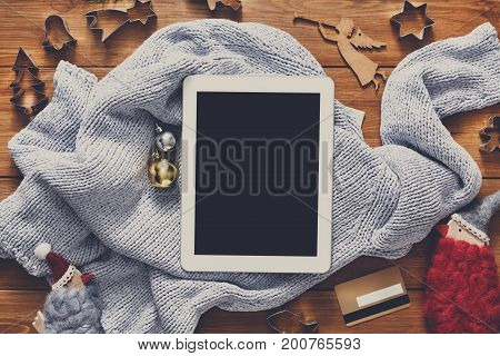 Christmas online shopping background. Tablet screen with copy space top view on wood, credit card and warm sweater. Electronic devices, internet commerce on winter holidays concept