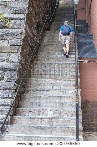 Man Walking Up a long Flight of Stairs