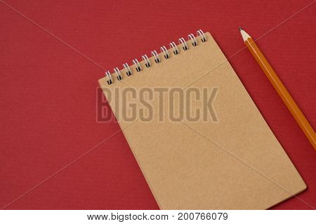 Top view of open spiral blank notebook with pencil on red paper background. Open vintage notebook. Empty notebook paper for text with  pencil . office concept top view.Copy space. Space for text.