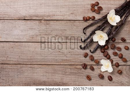 Vanilla sticks with coffee beans avd flower on a old wooden background with copy space for your text. Top view.