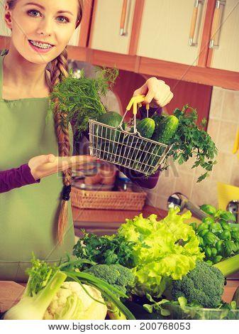 Woman In Kitchen Having Vegetables Holding Shopping Basket