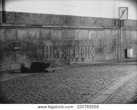 Prague, Czech Republic: old beggar man begging on his knees that night at cobblestone road. Next the wall tiles. Twilight. Road sign. Mess. A glass of money.