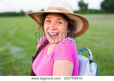 Portrait on cute funny laughing woman with freckles in hat showing thumbs up gesture.