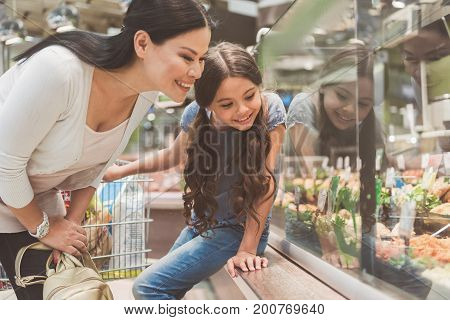 Glad mother is inclining to shop-window of different eatable goods. Little curious daughter sitting at special shelf. Low angle