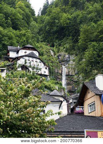Town Hallstatt with mountain waterfall. Alpine massif, beautiful canyon in Austria. Salzburg Alpine valley in summer, clear water. Destination for vacation, hiking and relaxation.