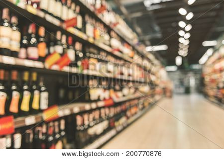 Various sorts of wine are on shelves at big modern store. Defocused picture. Copy space