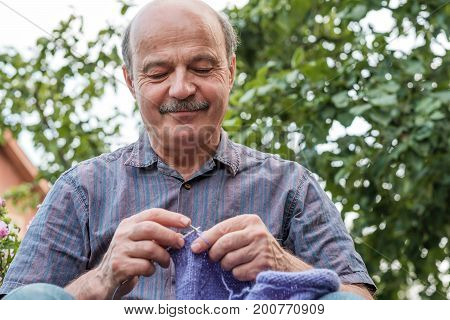 people and needlework concept - man hands knitting with needles and blue yarn